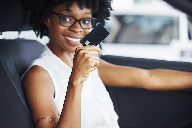 Détient une carte de crédit. une jeune femme afro-américaine est assise à l'intérieur d'une nouvelle voiture moderne.