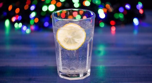 Détox après la fête d'hiver. concept de soins de santé. que boire à la fête de noël. verre à cocktail avec de l'eau et une tranche de lumières de guirlande défocalisée au citron. boisson détox pour se sentir mieux. gueule de bois et détox.