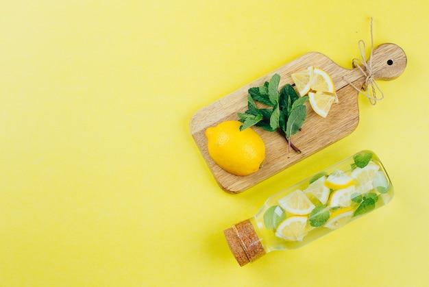 Detox citron menthe eau en bouteille de verre et ingrédients sur des planches à découper en bois sur fond jaune