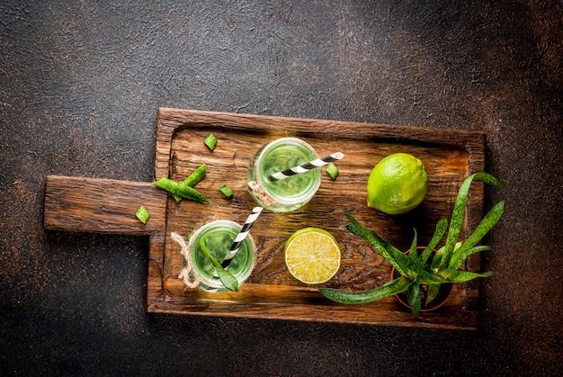 Détox exotique sain boire de l'aloe vera ou du jus de cactus au citron vert sur fond sombre