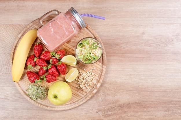 Détox nettoie la boisson, les fruits et les baies smoothie ingrédients. jus sain naturel et biologique pour régime amaigrissant ou journée de jeûne. pot mason de boisson diététique aux fraises, micro-verts et banane