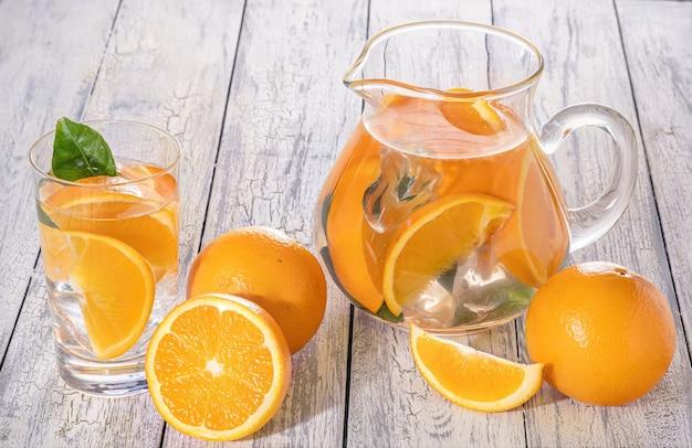 Detox orange saine avec orange fraîche et citron vert, en verre sur un mur en bois.