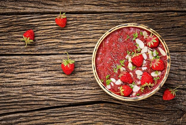Détox et petit déjeuner superaliments sains dans un bol. pudding de graines de chia végétaliennes aux fraises et aux amandes. smoothie aux fraises. vue de dessus. mise à plat
