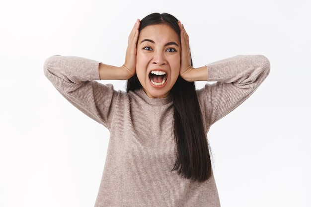 Détresse et marre, femme furieuse et alarmée déprimée, perdant le contrôle, souffrant d'une dépression nerveuse, criant attrape la tête et regarde la caméra avec douleur et colère, crie furieux, se tient debout sur un mur blanc