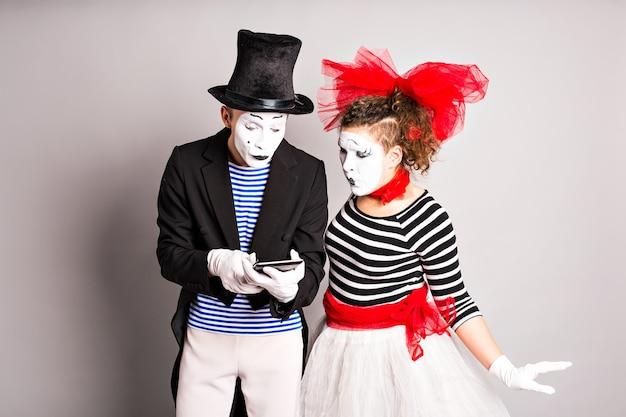 Deux acteurs utilisant une tablette numérique sur fond blanc. prise de vue horizontale.