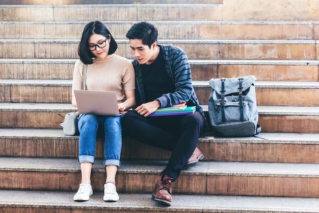 Deux, adolescent, étudiants, faire, devoirs, à, livres, et, ordinateur portable, s'asseoir, sur, escalier, à, université