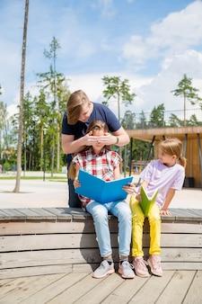 Deux adolescentes assis sur le banc et un garçon fermant les yeux à une fille