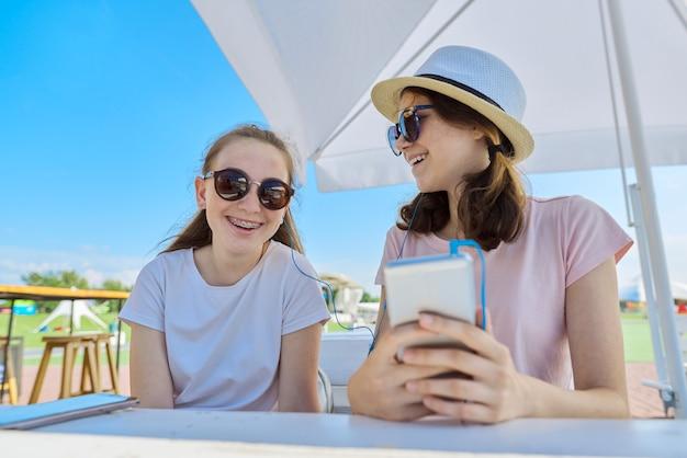 Deux adolescentes dans les écouteurs, écouter de la musique sur smartphone, s'amuser aux beaux jours d'été