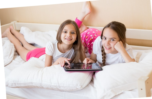 Deux adolescentes gaies allongées sur le lit et utilisant une tablette numérique