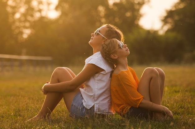 Deux adolescentes s'amusent dans le parc. deux amis en plein air. les gens d'été dans des verres