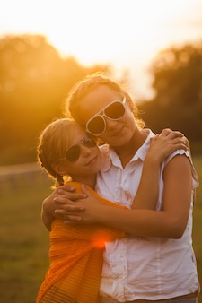 Deux adolescentes s'amusent dans le parc. deux amis en plein air. gens d'été dans des verres
