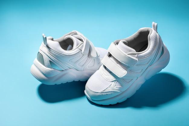 Deux adolescents blancs planant dans l'air des chaussures de course isolés sur un fond bleu avec des ombres dures