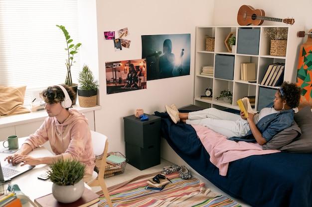 Deux adolescents contemporains reposants lisant un livre et réseautant dans la chambre