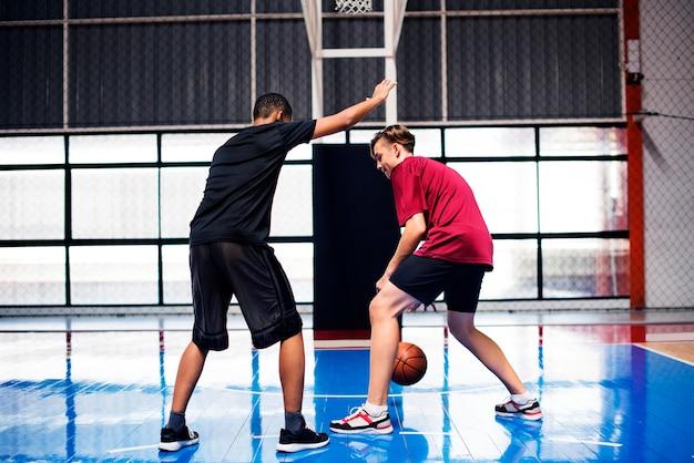 Deux adolescents jouant au basket ensemble sur le court