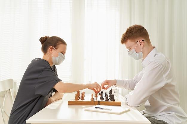 Deux adolescents jouent aux échecs pendant la quarantaine en raison de la pandémie de coronavirus