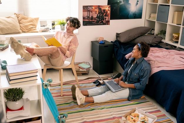 Deux adolescents lisant un livre et utilisant un ordinateur portable dans la chambre