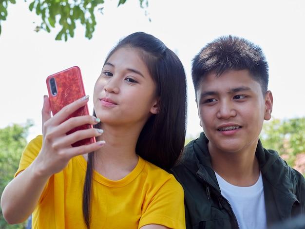 Deux adolescents utilisent leurs smartphones à l'extérieur
