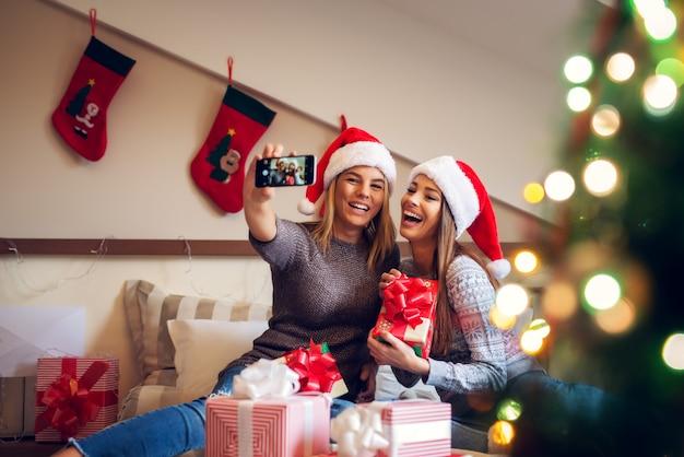 Deux adorables copines avec bonnet de noel assis sur le lit pour les vacances de noël l'une à côté de l'autre et prenant un selfie en riant de louanges.