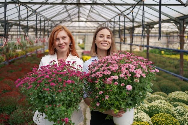 Deux adorables dames posant avec un bouquet de chrysanthèmes roses dans une belle maison verte fleurie avec toit en verre.