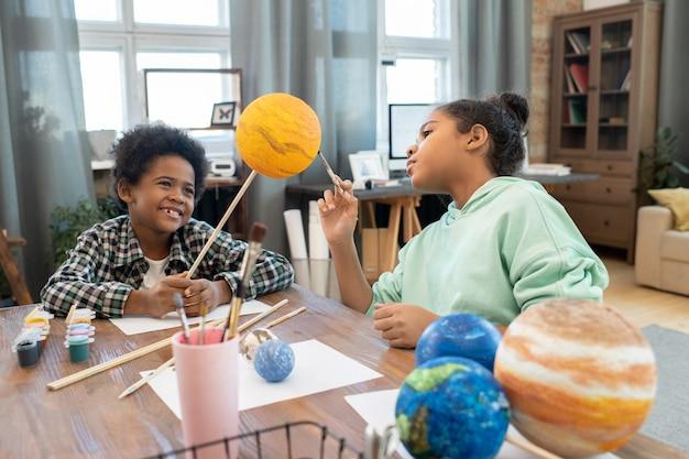 Deux adorables écoliers métis en tenue décontractée peignant des planètes tout en se préparant à une leçon d'astronomie par table dans un environnement domestique