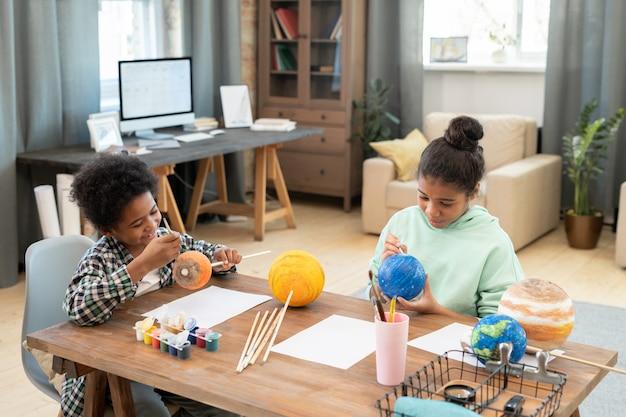 Deux adorables frères et sœurs d'âge élémentaire peignant des planètes assis près d'une table dans un environnement domestique et se préparant à la leçon d'astronomie