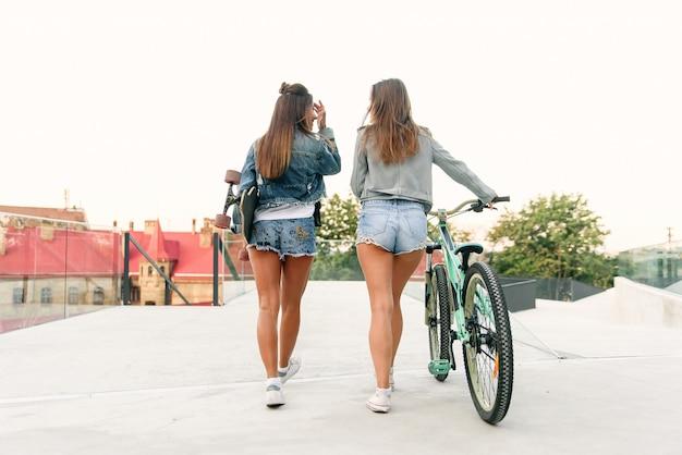 Deux adorables meilleures copines en vestes en jean élégantes et shorts en jean avec vélo et longboard tout en marchant dans la rue le matin.