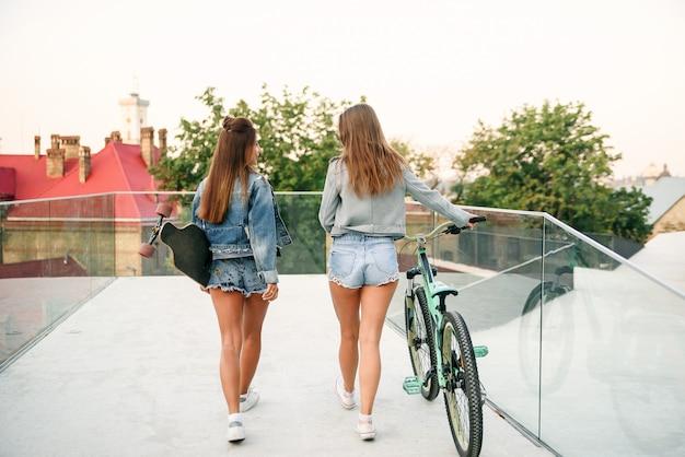 Deux adorables meilleures petites amies dans des vestes en jean élégantes et un short en jean avec vélo et longboard tout en marchant dans la rue le matin.