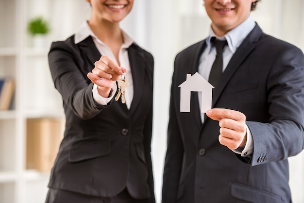 Deux agents immobiliers en costume montrent un modèle de maison et des clés.
