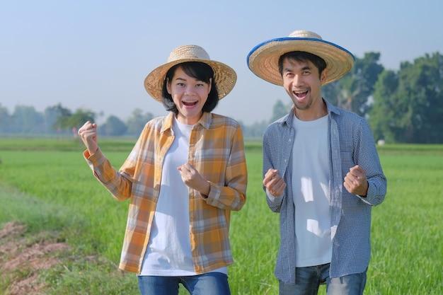 Deux agriculteurs asiatiques posent une joyeuse surprise dans une ferme de riz vert. concept de couple d'agriculteurs.