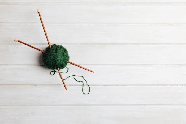 Deux aiguilles en boule de laine verte