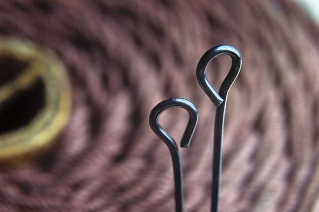 Deux aiguilles de tailleur dans une bobine de fil marron. macro.