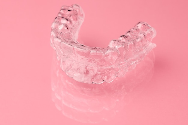 Deux aligneurs de dents dentaires invisibles sur fond rose. orthèses amovibles temporaires orthodontiques pour la fixation des dents après alignement. thérapie après parenthèses.