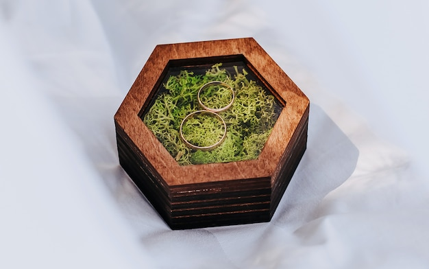Deux alliances dans une boîte en bois avec une mousse sur fond blanc avec voile