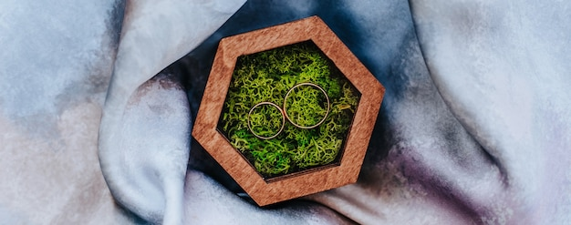 Deux alliances dans une boîte en bois avec une mousse végétale sur fond de tissu violet