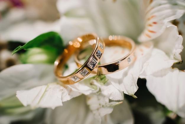 Deux alliances en or avec diamants se trouvent sur un bouquet floral