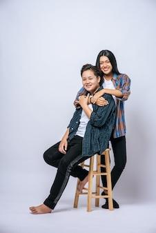 Deux amantes attrapent une autre épaule et s'assoient sur une chaise.