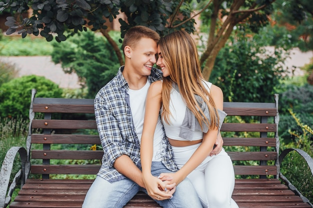 Deux amants assis sur un banc dans un parc et se tenant par la main.