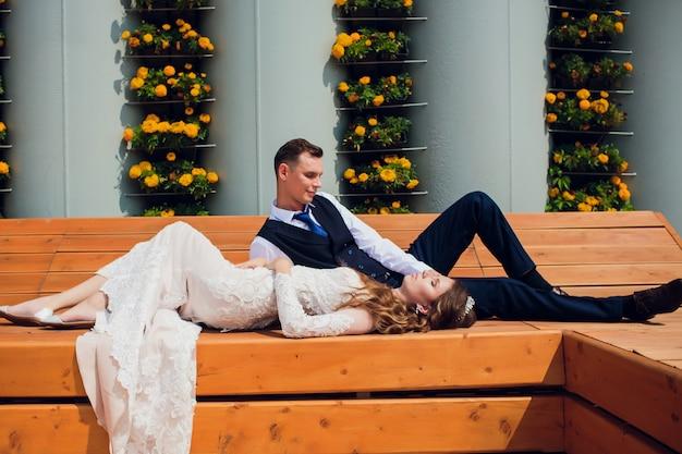 Deux amants sont assis sur un banc, les jeunes mariés accroupis pour se reposer dans les bras l'un de l'autre lors d'une séance photo de mariage, la mariée en robe blanche et le marié dans un beau costume retiré dans le parc.