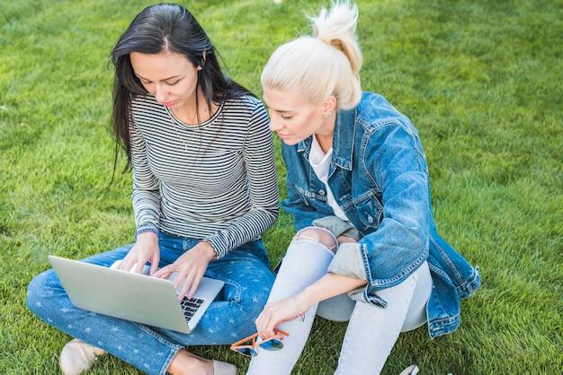 Deux amies assis sur l'herbe verte à l'aide d'un ordinateur portable