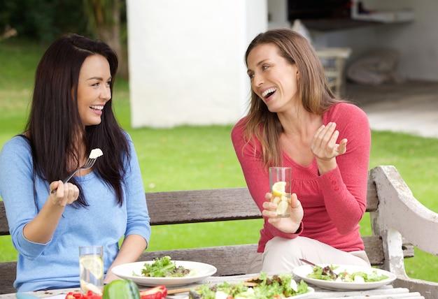 Deux amies assises dehors dans le jardin en train de déjeuner