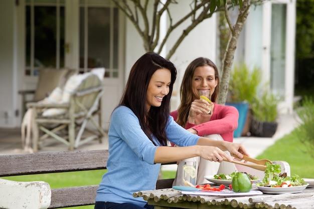 Deux amies assises dehors en train de déjeuner