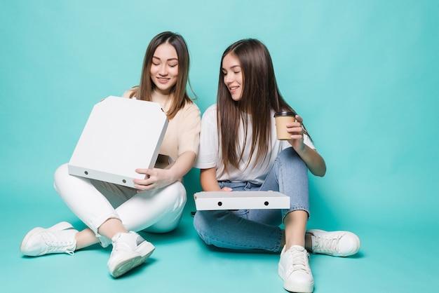 Deux amies assises sur le sol boivent du café pour aller manger de la pizza isolée sur un mur turquoise