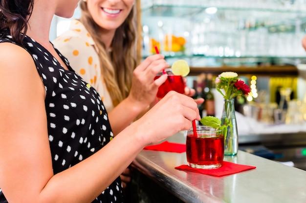 Deux amies au café bar buvant un long drink