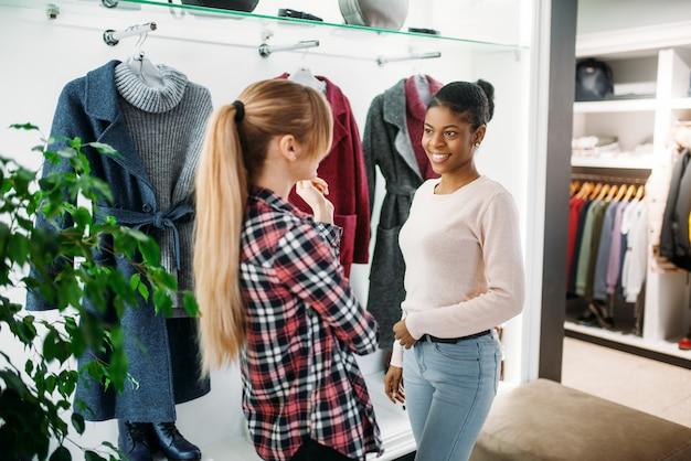 Deux amies choisissant manteau en boutique