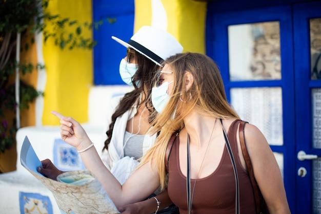 Deux amies debout dans la ville regardant une carte touristique et portant des masques faciaux. tourisme pendant le concept de temps de pandémie
