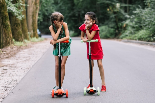 Deux amies debout avec push scooter sur rue