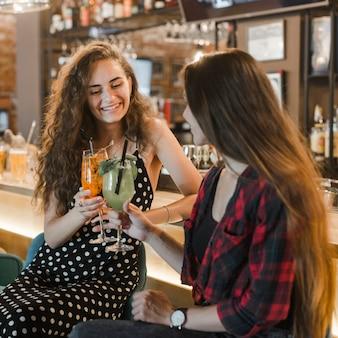 Deux amies grillent des verres de cocktails au bar