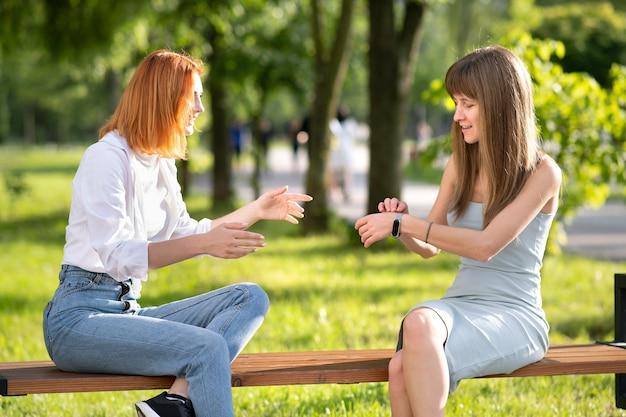 Deux amies heureuses assises sur un banc à l'extérieur dans un parc d'été discutant joyeusement en s'amusant.