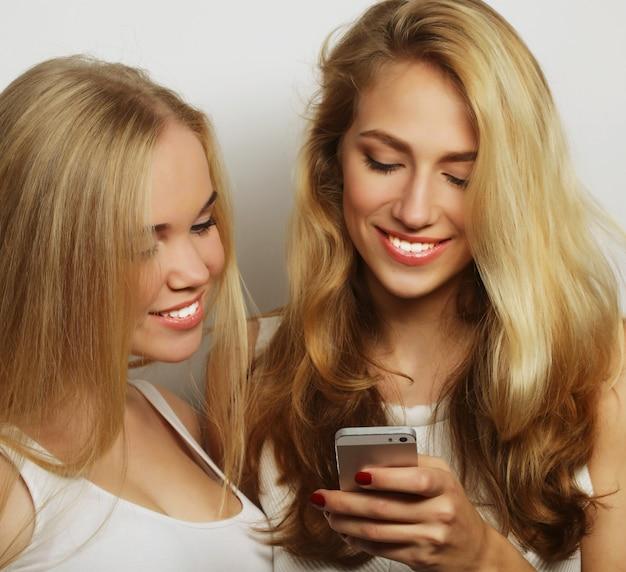 Deux amies heureuses partageant les médias sociaux dans un téléphone intelligent, sur fond gris