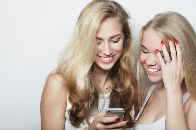 Deux amies heureuses partageant les médias sociaux dans un téléphone intelligent sur fond gris